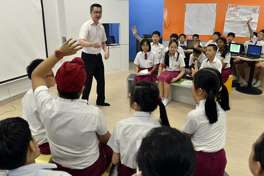 A teacher conducting a lesson with a class of Primary 6 pupils at Woodlands Primary School in 2012. Singapore has once again topped the biggest global school rankings published by the Organisation for Economic Co-operation and Development. -- PHOTO: