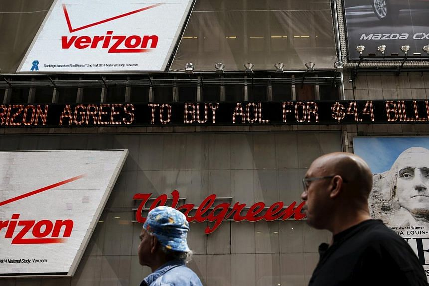 People walk by the Dow Jones electronic ticker at Times Square in New York, May 12, 2015. Wall Street stocks finished lower Wednesday as worries over higher US Treasury bond yields offset Verizon's US$4.4 billion (S$5.8 billion) takeover of AOL.