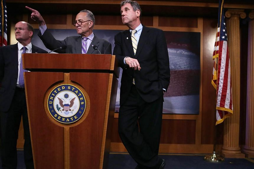 US Senator Charles Schumer (D-NY) taking questions as Senator Sherrod Brown (D-OH) (right), and Senator Chris Coons (D-DE) (left) look on during a news conference on May 12, 2015, on Capitol Hill in Washington, DC. US senators reached a deal Wednesda