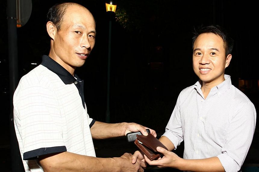 Construction worker Cui Hua Bi (left) and Mr Sean Lee. Mr Lee waited for close to three hours to return $10,000 to Mr Cui. -- PHOTO: WAN BAO FILE