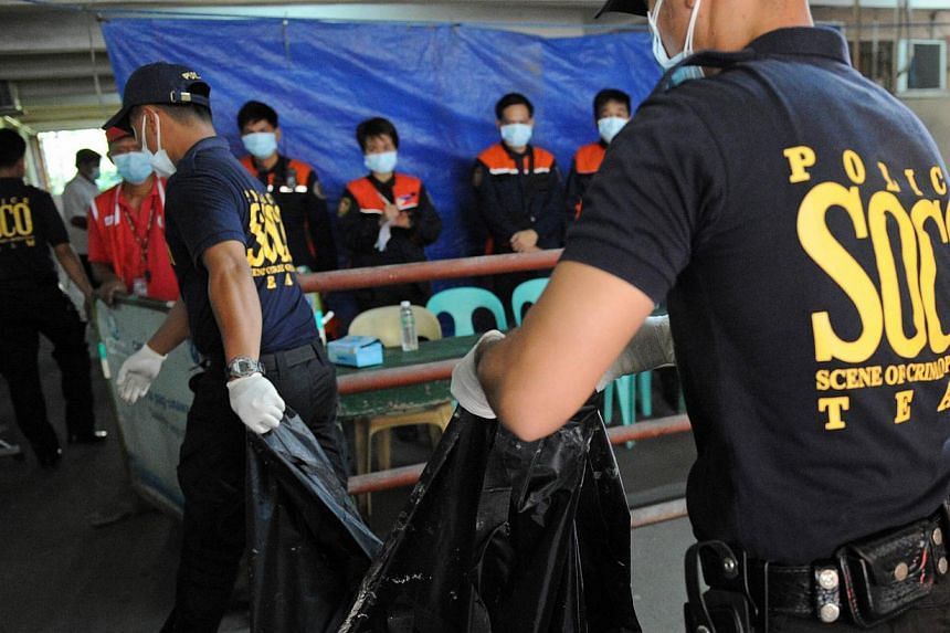 A police forensics team carrying a body bag containing the remains of a victim killed in a fire that gutted a footwear factory in Valenzuela city in suburban Manila on May 14, 2015. -- PHOTO: AFP