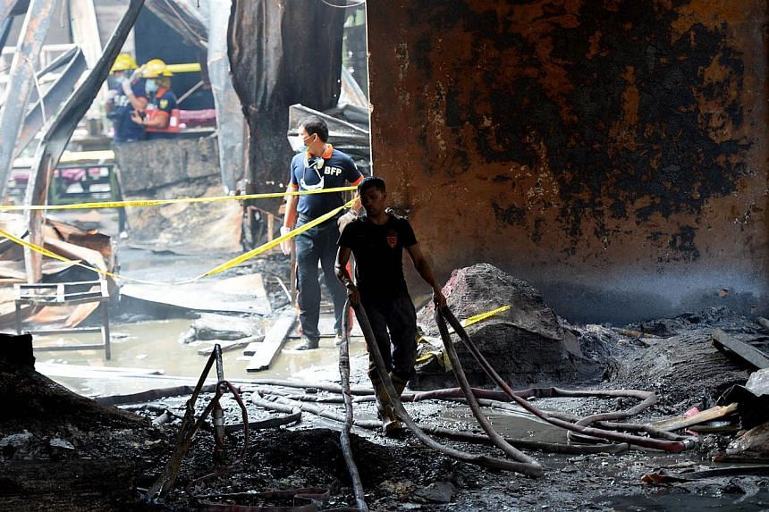 Fire investigators looking for evidence among the ruins of a footwear factory in suburban Manila on May 14, 2015. -- PHOTO: AFP