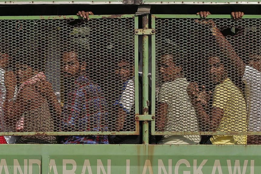 Bangladeshi and Rohingya migrants arriving in a truck at a naval base in Langkawi on May 14, 2015. More vessels bearing hungry migrants are headed towards Malaysia, which has beefed up sea and air patrols off its north-eastern coast to prevent them l