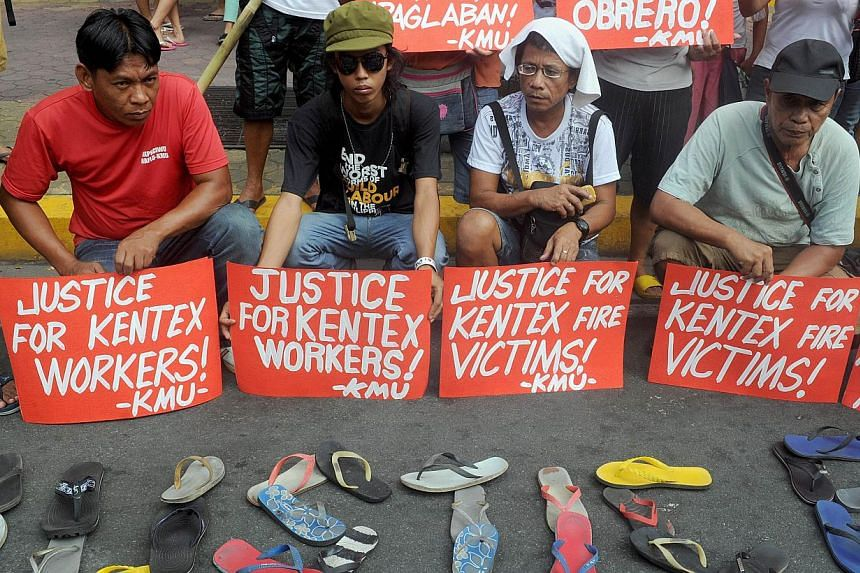Protesters holding placards, while displaying sandals on the ground, during a rally to call for justice for the victims of a fire that gutted a footwear factory the day before, in Manila on May 14, 2015. -- PHOTO: AFP