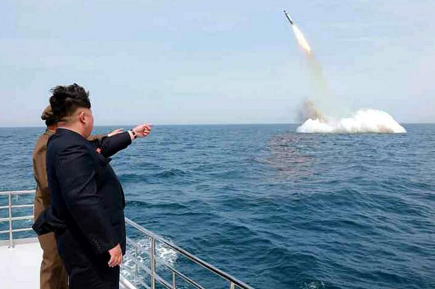 An image obtained by Yonhap News Agency shows North Korean leader Kim Jong Un pointing at a submarine-launched ballistic missile near Sinpo, on the north-east coast of North Korea on May 9, 2015. -- PHOTO: EPA
