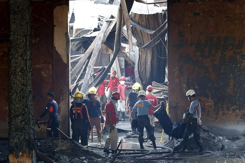 Police carrying a body bag containing a body of a victim as workers remove debris in a gutted slipper factory in Valenzuela, Metro Manila in the Philippines on May 14, 2015. -- PHOTO: REUTERS