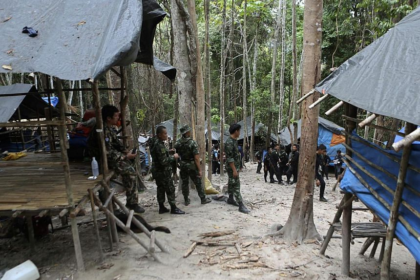 Thai soldiers securing the area next to shelters after discovering another abandoned jungle camp believed used by the human traffickers to detain Rohingya migrants at a mountain in Sadao, Thai-Malaysian border district, Songkhla province, southern Th
