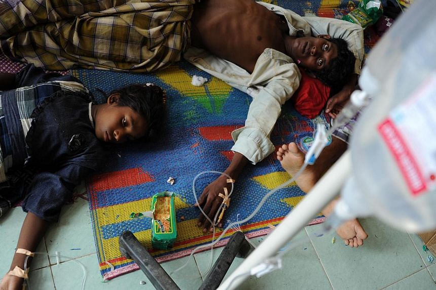 Rescued migrants receiving medical treatment at a temporary shelter in a government sports auditorium in Lhoksukon in Aceh province on May 12, 2015, after Indonesian rescuers found their boat carrying 573 passengers mostly Rohingya from Myanmar and B