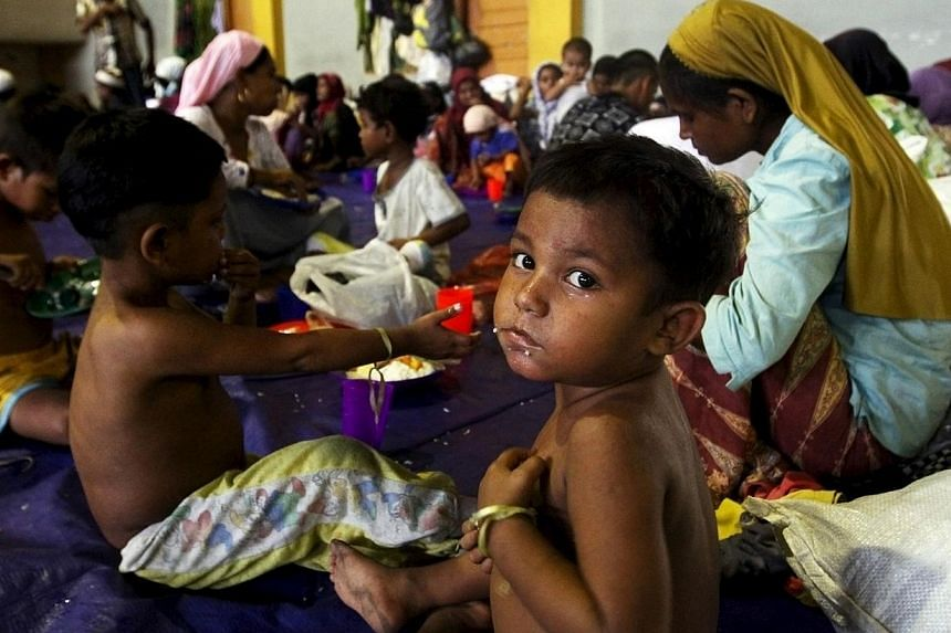 A child, believed to be Rohingya, eating inside a shelter after he was rescued along with hundreds of others on Sunday from boats in Lhoksukon, Indonesia's Aceh Province on May 12, 2015. -- PHOTO: REUTERS