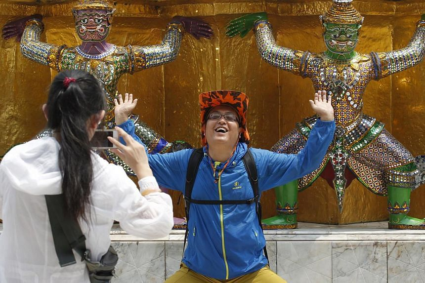 A Chinese tourist posing with statues in the Grand Palace in Bangkok. Public outrage over the poor behaviour of Chinese visitors forced the Thai government to issue thousands of Chinese-language etiquette manuals last month, while the Chinese governm
