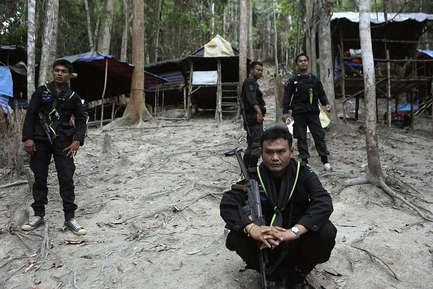 Thai soldiers securing an abandoned jungle camp believed to have been used by human traffickers to detain Rohingya migrants at a mountain in Sadao, Songkhla province, southern Thailand, on May 12, 2015. -- PHOTO: EPA