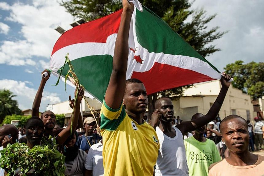 Men hold a Burundi's flag as people take to the streets to celebrate, waving branches, beeping car horns and parading through Bujumbura on May 13, 2015 following the radio announcement by Major General Godefroid Niyombare that President Nkurunziza wa