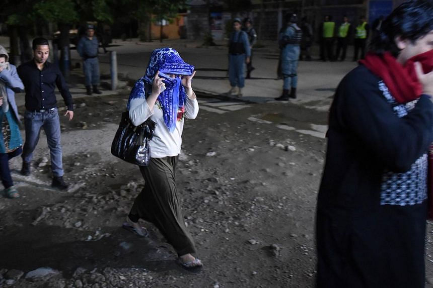Afghan guests who were stuck inside a Kabul guesthouse walk after they were rescued by the security forces on May 13, 2015. -- PHOTO: AFP