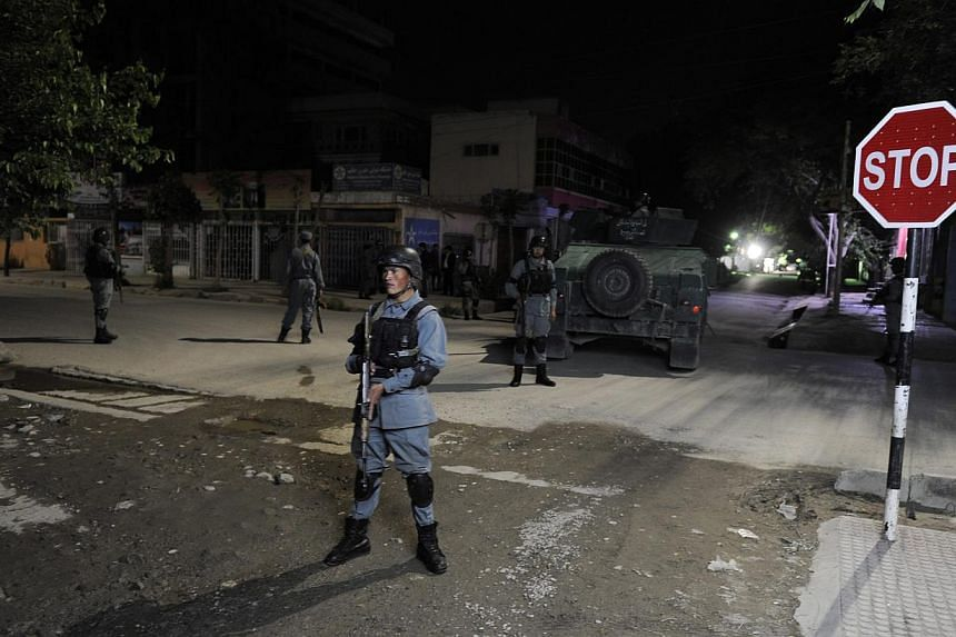 Afghan security officials secure the scene of a gunfight between militants and Government forces near a guest house in Kabul, Afghanistan on May 13, 2015. -- PHOTO: EPA