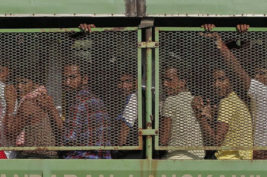 Bangladeshi and Rohingya migrants are seen in a truck as they arrive at a naval base before being transferred to Kuala Kedah jetty with the navy ship 'KD Mahawangsa', in Langkawi, Malaysia on May 14, 2015. -- PHOTO: EPA