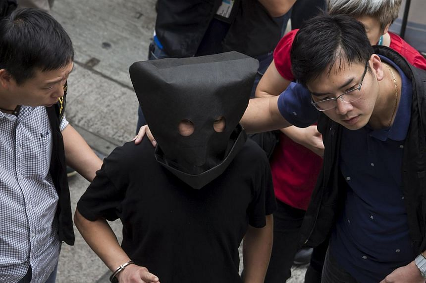 Police officers escorting a man suspected to be involved in the kidnapping in Hong Kong on May 5, 2015. -- PHOTO: REUTERS