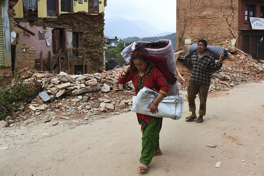 Nepalese residents carry their belongings as they walk past destroyed buildings in the town of Chautara in north-eastern Nepal in the aftermath of two earthquakes in the span of three weeks that shook the country. -- PHOTO: AFP