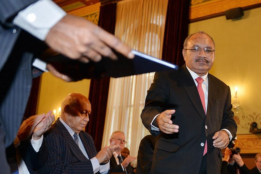 Papua New Guinea Prime Minister Peter O'Neill (right) receives his papers as he prepares to give a talk at the Lowy Institute in Sydney on May 14, 2015.Mr O'Neill on Thursday said he was shocked by an announcement from former colonial rul