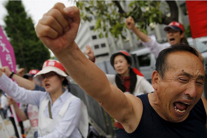 Protesters shouting slogans during a rally against Japan's Prime Minister Shinzo Abe's Cabinet approving Japan security Bills, in front of Abe's official residence in Tokyo on May 14, 2015. -- PHOTO: REUTERS