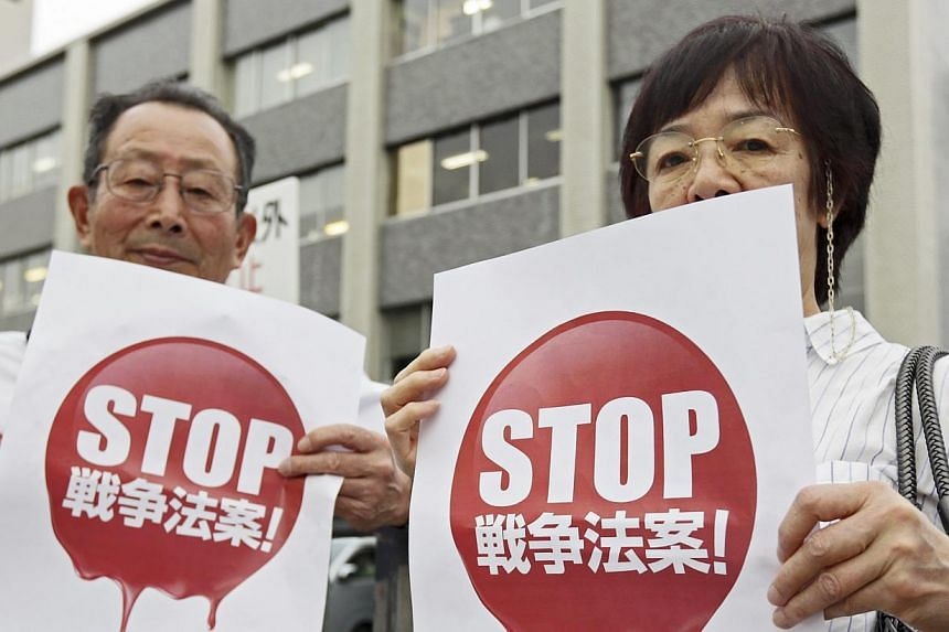 Demonstrators protesting against Japanese Prime Minister Shinzo Abe's Cabinet decision to change Japan's post-World War II defence security policy outside the prime minister's official residence in Tokyo, Japan, on May 14, 2015. -- PHOTO: EPA