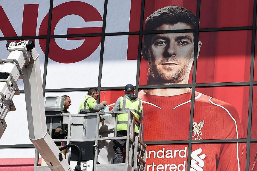 Workmen work on a poster of Liverpool's English midfielder Steven Gerrard outside The Kop stand at Anfield, Liverpool, on May 13, 2015.Tickets to the game, Gerrard's final home appearance, which usually cost 47 pounds (S$98),are on