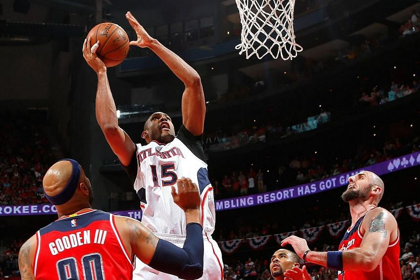 Al Horford #15 of the Atlanta Hawks shoots over (from left) Drew Gooden #90, Ramon Sessions #7, and Marcin Gortat #4 of the Washington Wizards during Game Five of the Eastern Conference Semifinals of the 2015 NBA Playoffs at Philips Arena on May 13,