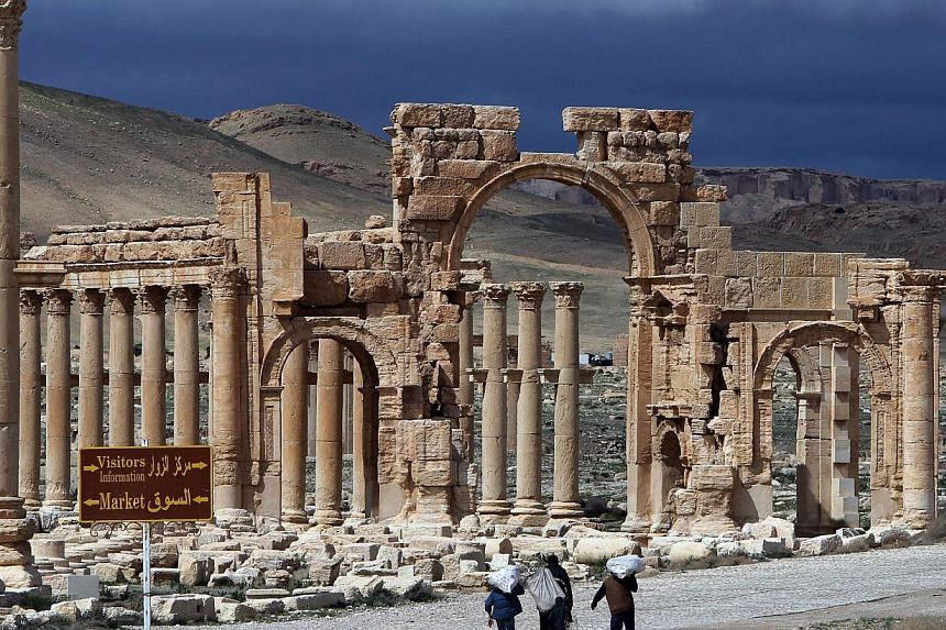 Syrian citizens walking in the ancient oasis city of Palmyra, 215km north-east of Damascus, on March 14, 2014. Islamic State in Iraq and Syria (ISIS) group fighters advanced to the gates of ancient Palmyra Thursday, raising fears the Syrian world her