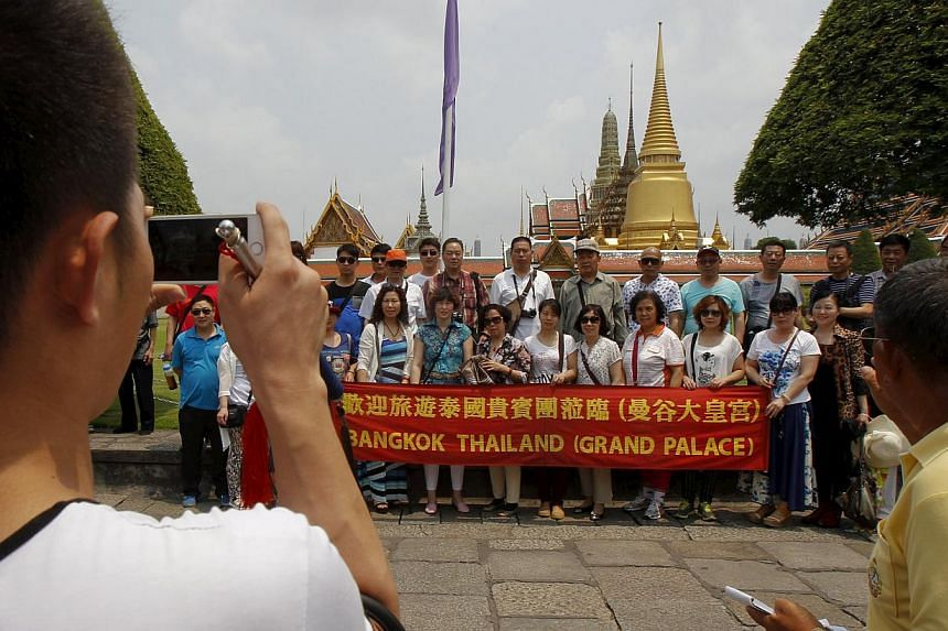 Chinese tourists pose for photos as they visit Wat Phra Kaeo (Emerald Buddha Temple) in Bangkok on March 23, 2015.A Chinese company is sending more than 12,000 people on a holiday to Thailand, tourism officials said Thursday, with one resort ho