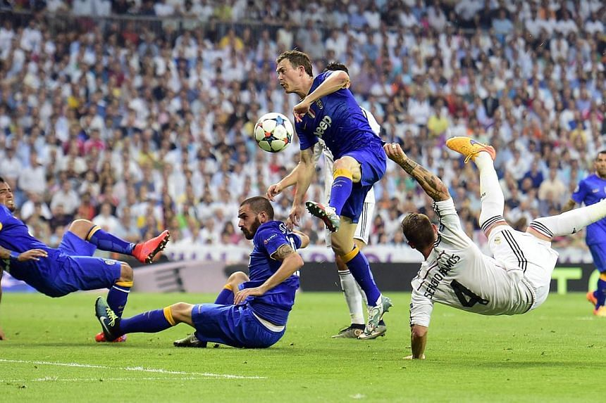 Real Madrid defender Sergio Ramos (right) kicks the ball past Juventus defenders Leonardo Bonucci (second left) and Stephan Lichtsteiner (second right) and midfielder Arturo Vidal during the Champions League semi-final on May 13, 2015. -- PHOTO: AFP&