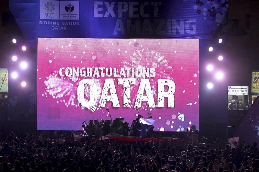 "People celebrate in front of a screen that reads ""Congratulations Qatar"" after Fifa announced that Qatar will be host of the 2022 World Cup in Souq Waqif in Doha in this Dec 2, 2010 file photo. Fifa on Wednesday banned former vice-president Reynald T"