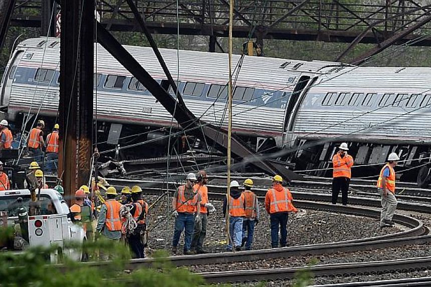 Rescuers work near the wreckage of Amtrak train from Washington to New York that derailed yesterday May 13, 2015 in north Philadelphia, Pennsylvania. -- PHOTO: AFP