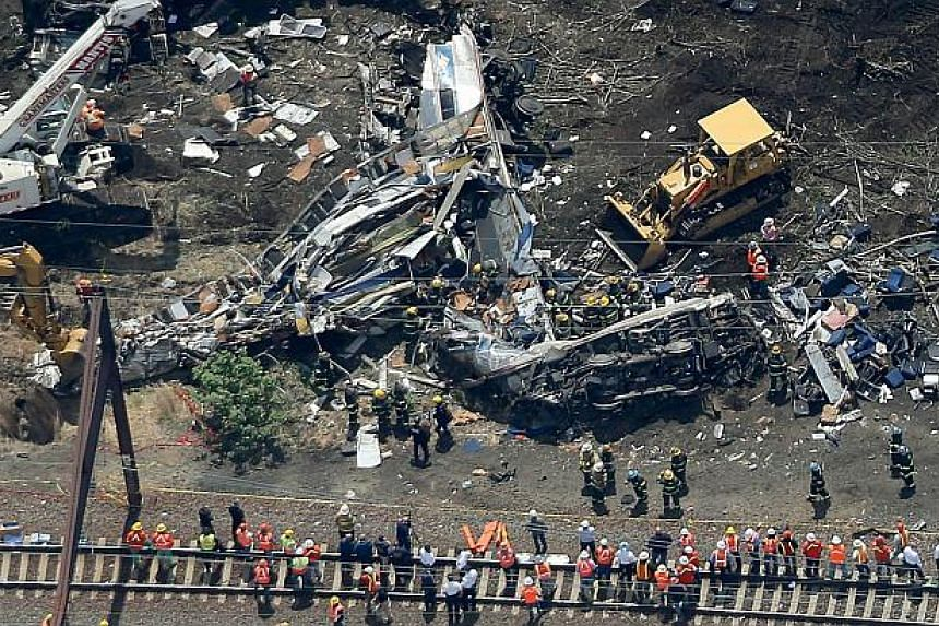 Investigators and first responders work near the wreckage of Amtrak train from Washington to New York that derailed yesterday May 13, 2015 in north Philadelphia, Pennsylvania. -- PHOTO: AFP