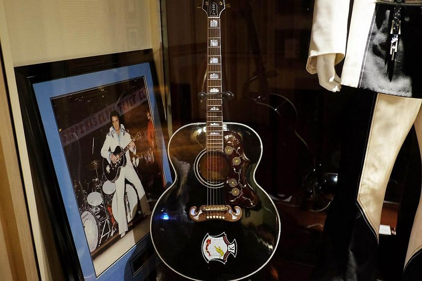 Elvis Presley's J-200 guitar and framed photograph on display at the Hard Rock Cafe in New York on May 11, 2015. The guitar is among the music memorabilia to be auctioned by Julien's Auctions on May 15 and 16 in New York. -- PHOTO: AFP