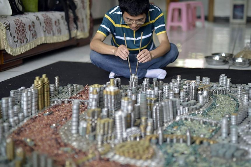 He Peiqi, a resident of Chongqing City, building a replica of his home town with coins and agate stones at his home on April 29, 2015. -- PHOTO: AFP