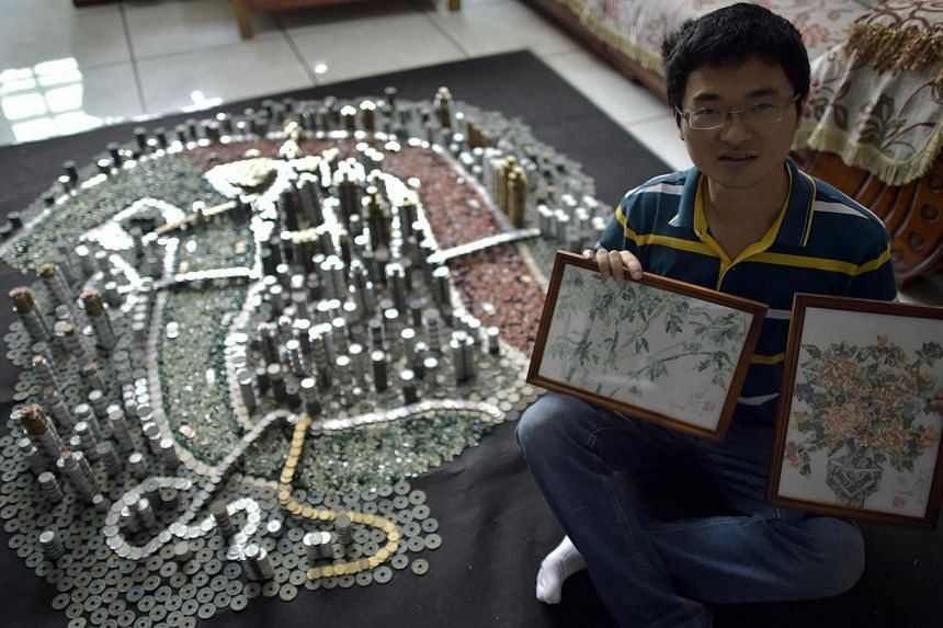 He Peiqi sitting next to the replica he built as he holds two paintings he made from various banknotes. -- PHOTO: AFP