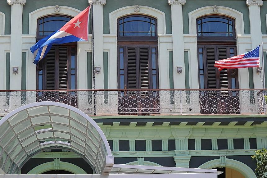A Cuban and US flag on the balcony of a hotel in Havana on April 13, 2015. US and Cuban negotiators will meet next week to discuss the reopening of embassies in each other's capitals as part of efforts to restore diplomatic ties. -- PHOTO: AFP