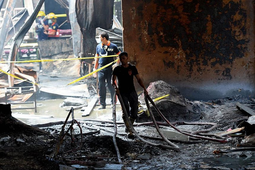 Fire investigators looking for evidence amongst the ruins of a footwear factory in suburban Manila on May 14, 2015, a day after the it was gutted by fire. -- PHOTO: AFP