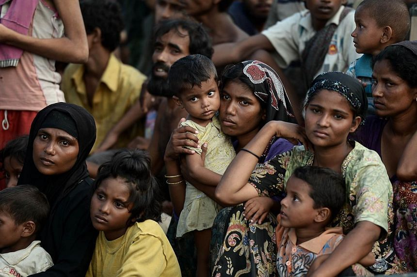 Rohingya migrants on a boat drifting in Thai waters off the southern island of Koh Lipe in the Andaman sea on May 14, 2015. Around 900 Rohingya and Bangladeshi migrants arrived in Indonesia and Thailand on Friday. -- PHOTO: AFP
