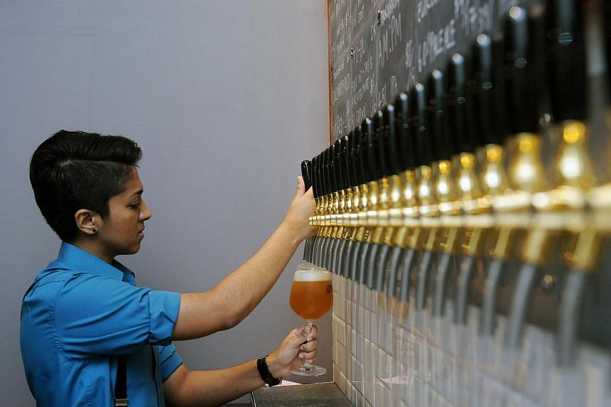"""Druggists """"beertender"""" Trisha Pillai pouring beer from one of the 23 taps behind the counter. -- PHOTO: TIFFANY GOH"""