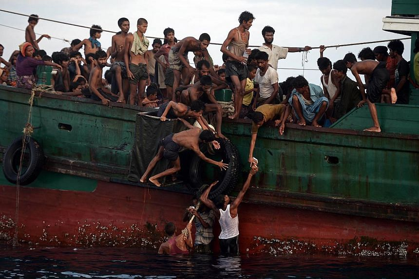 Rohingya migrants passing food supplies dropped by a Thai army helicopter to others aboard a boat off the southern island of Koh Lipe yesterday. The boat was found drifting in Thai waters, with passengers saying several people had died over the last