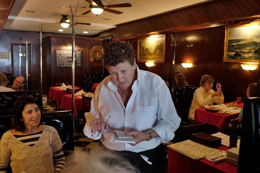Maureen Donohue-Peters, a waitress at Donohue's Steak House, works in the restaurant in New York on May 14, 2014.Robert Ellsworth, an art collector and a regular to the restaurant who died at the age of 85 in August, left US$100,000 in his will