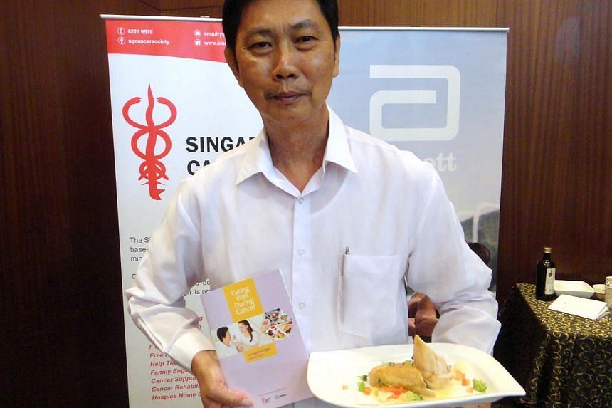 Mr Ricky Chiu, 61, posing with the Singapore Cancer Society's booklet with tips to help cancer patients eat right, and a sample of a meal suited to a cancer patient. Mr Chiu was diagnosed with throat cancer in 1997, but has since fully recovered. --