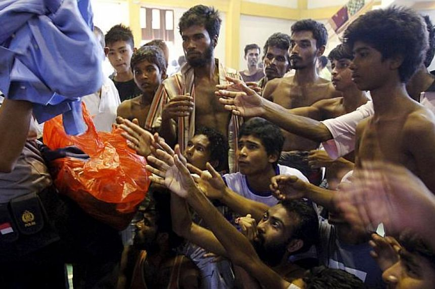 An Indonesia policeman distributes used clothes to migrants believed to be Rohingya inside a shelter in Lhoksukon, in Indonesia's Aceh province on May 11, 2015. -- PHOTO: REUTERS