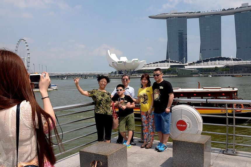 A lady taking a group photograph for tourists from China at the Merlion. It will be less of a hassle for some travellers from China to visit Singapore from June 1. -- ST PHOTO: LIM SIN THAI