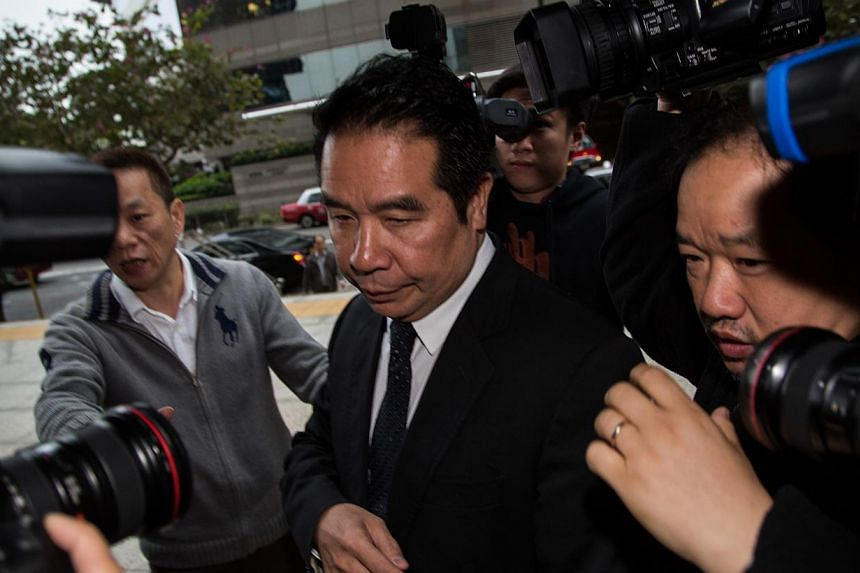Carson Yeung, owner of Birmingham City Football Club and former chairman of Birmingham International Holdings Ltd., is surrounded by members of the media as he enters the Wanchai Law Courts in Hong Kong, China, on Friday, Feb. 28, 2014. -- PHOTO: ST