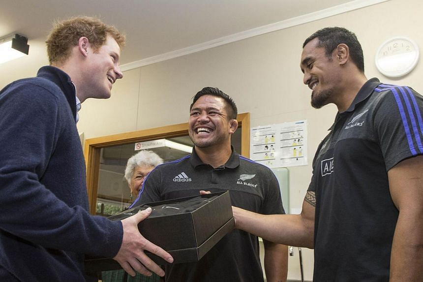 Britain's Prince Harry (left) is presented with an New Zealand All Black rugby jersey by All Blacks Jerome Kaino (right) and Keven Mealamu (centre) on a visit to the Auckland Spinal Rehabilitation Unit in Auckland on May 15, 2015. -- PHOTO: AFP