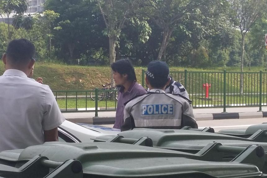 The male bus driver being led away by police officers. -- ST PHOTO: PRISCILLA GOY