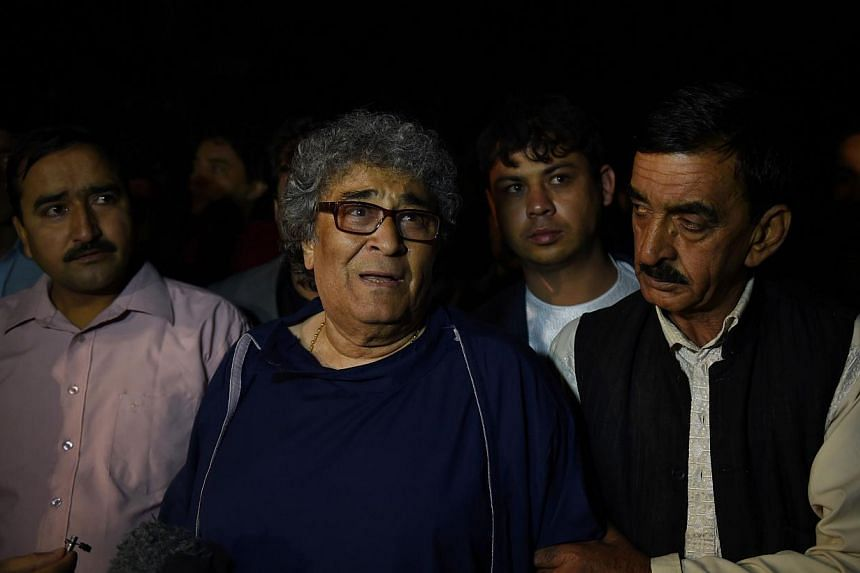 Afghan classical singer Altaf Hussain (centre) who was due to host a concert walks after being rescued by security forces at the Park Place guesthouse in Kabul on May 14, 2015.Fourteen people, most of them foreigners, were killed in a Taleban a