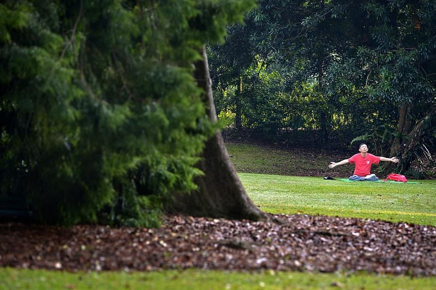 A man finishing his meditation on the open green at the Singapore Botanic Gardens. -- ST PHOTO: KUA CHEE SIONG