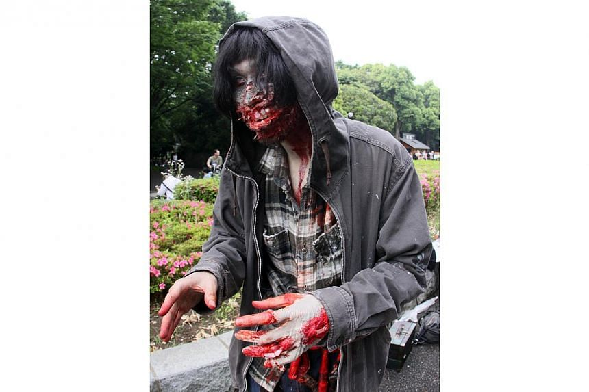 A participant takes part in a 'zombie walk' at a park in Tokyo on May 16, 2015. -- PHOTO: AFP